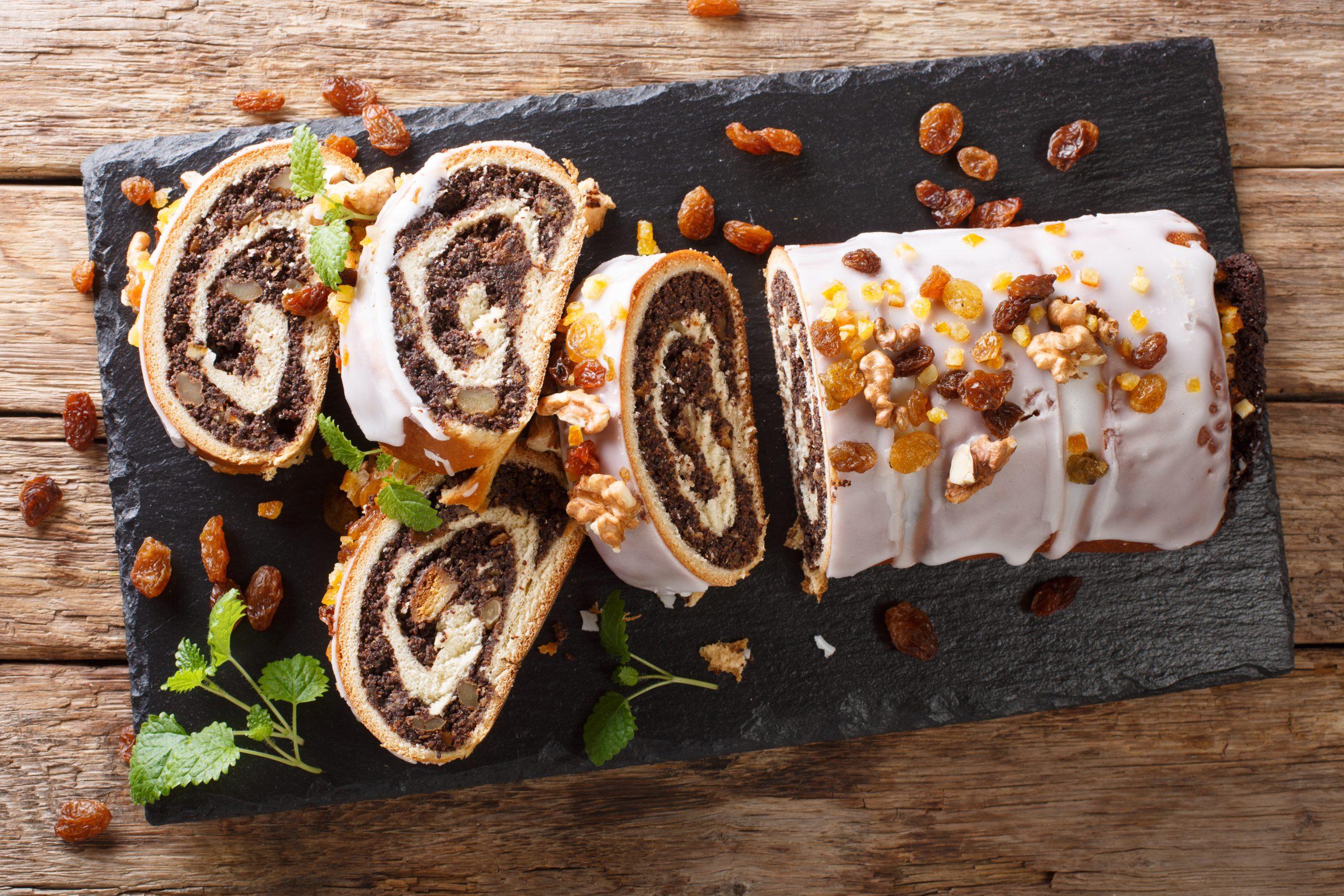 Festive glazed poppy beigli cake with raisins, walnuts close-up on a table. Horizontal top view
